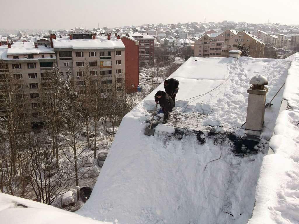 Čišćenje snega sa krova zgrade, prokišnjavanje krova